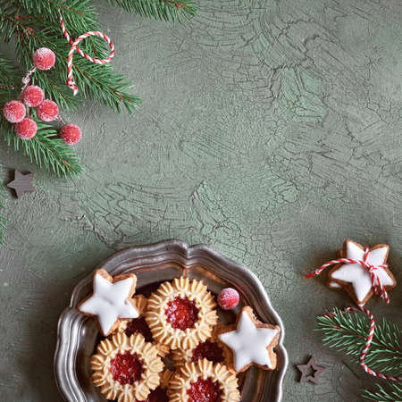 Flat lay with Xmas decorations in green and red with frosted berries, trinkets and Christmas cookies, text space