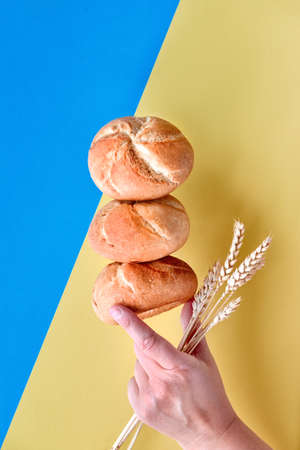 Pyramid of rusty round bread rolls (Kaiser or Vienna rolls), balancing on each other with hand holding wheat ears on blue and yellow colored paper background Archivio Fotografico - 128379227