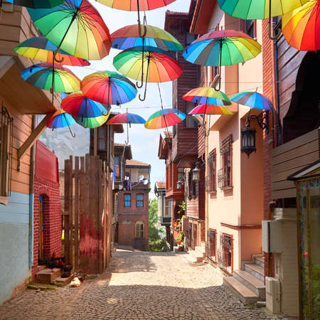 Narrow pedestrian street in Istanbul, Turkey, with rainbow umbrellas on display above the walkaway