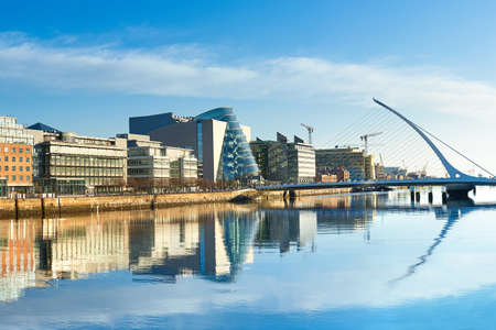 Modern buildings and offices on Liffey river in Dublin on a bright sunny day, bridge on the right is a famous Harp bridge. Banque d'images - 128379321