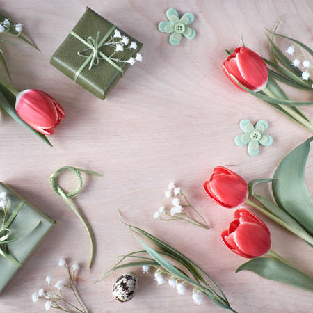Overhead view of light wooden table with springtime decorations, wrapped gifts, white flowers, red tulips and and Easter eggs. Spring or Easter background concept.