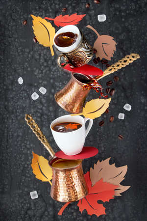 Balancing pyramid of jezves, turkish coffee pots and cups on dark background with coffee beans and sugar