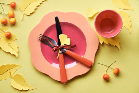 Table setup for Autumn celebration, Thanksgiving or birthday. Bright plastic plate with fork and knife on yellow paper with paper Autumn leaves and berries