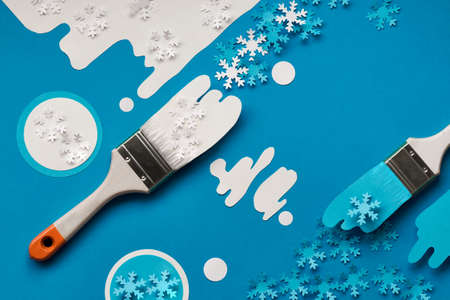Concept top view flat lay background in blue and white with brushes loaded with paper snowflakes