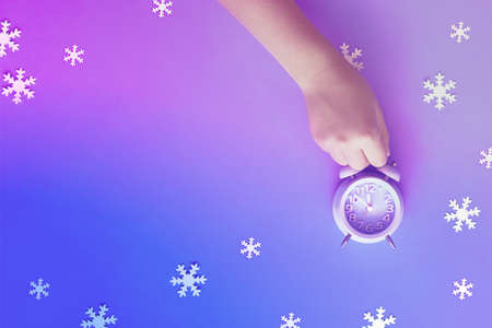 Die Hand des Kindes, die den Wecker hält, der fünf bis zwölf mit Papierschneeflocken zeigt. Silvesternacht, Mitternacht. Flaches Konzeptbild, Draufsicht auf neonfarbenem lila-blauem Hintergrund mit Kopienraum.