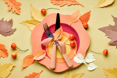 Table setup for Autumn celebration, Thanksgiving or birthday. Bright plastic plate with fork and knife on yellow paper with paper Autumn leaves Stock Photo