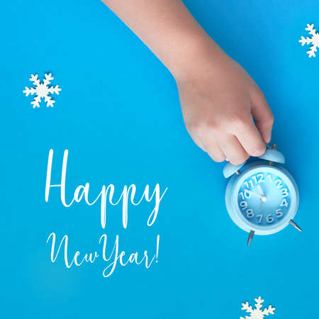 Child's hand holding blue alarm clock showing five to twelve with paper snowflakes. New Year's night, midnight, flat lay concept image, top view on pastel blue paper background.