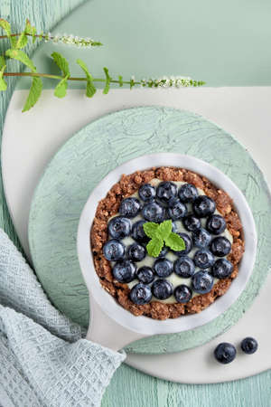 Flat lay of delicious Blueberry tartlet with vanilla custard cream and mint leaf on mint colored crackle wooden background