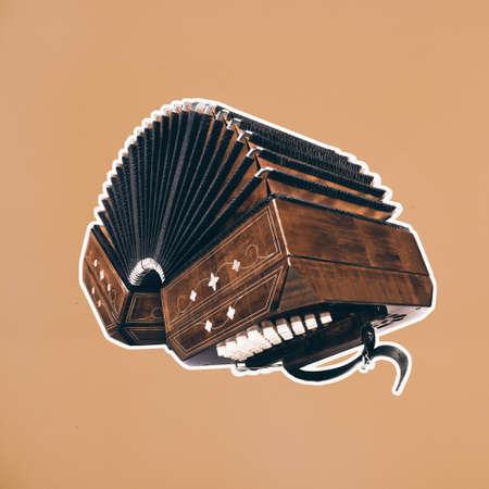 Bandoneon, tango instrument, with white border on square orange paper. Retro Argentine tango collage in magazine style