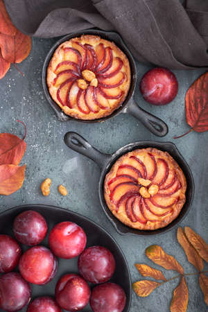 Homemade crumble tarts with plum slices baked in small iron skillets. Top lay on dark textured background with some plums, peanuts and red leaves