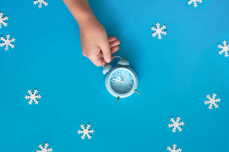 Child's hand holding blue alarm clock showing five to twelve with paper snowflakes. New Year's night, midnight, flat lay concept image, top view on pastel blue paper background. Stock Photo