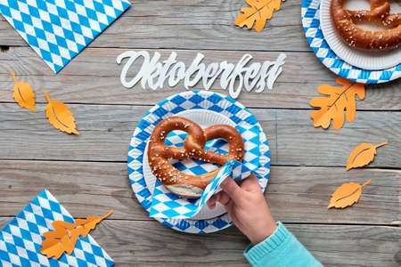 Oktoberfest, flat lay on rustic wooden table with pretzels on blue and white checkered disposable paper plates and orange Autumn leaves