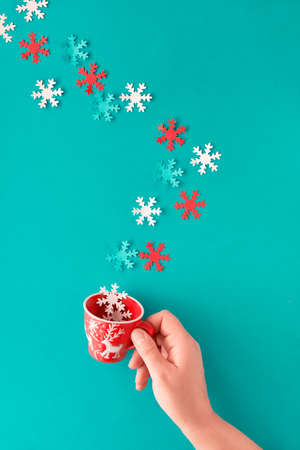Winter time or Christmas concept flat lay. Woman's hand holding cup with red and white seasonal decorations with a trail of snowflakes coming towards it. Flat lay, top view on pastel blue paper background. Stock Photo