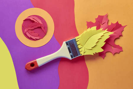 Top view on flat lay with brush loaded with paint made from paper Autumn leaves. Concept home renovation background in red, yellow, orange purple and coral colors