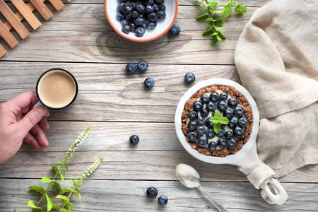 Flat lay of delicious Blueberry tartlets with vanilla custard cream, flat lay on light rustic wooden background with cotton fabric and female hand holding coffee.