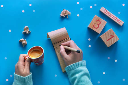 Christmas do list and womans hands with pen, notebook, calendar and coffee on blue pastel table top view. Flat lay style, blue paper background with snowflakes. Holiday planning concept.