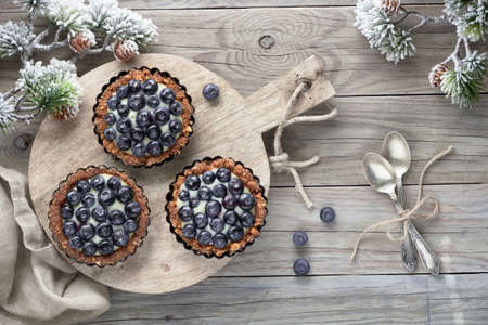 Winter blueberry tarts, flat lay on rustic wooden table decorated with pine twigs