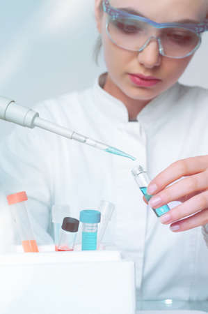 Young female scientist loads liquid sample into disposable plastic vial, scientific background with copy-space, shallow DOF, focus on the vial and pipette tip.