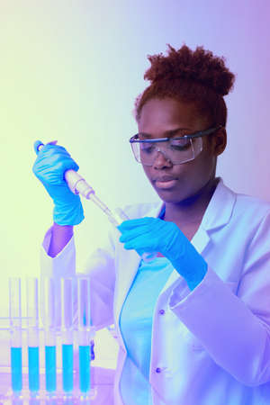 African scientist or graduate student in lab coat and protective wear works with automatic pipette in modernl laboratory. Futuristic neon glow, abstract light pattern in purple, blue and yellow, text