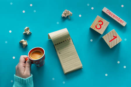 Christmas do list with pen, craft paper notebook, wooden calendar and coffee on blue pastel table top view. Flat lay style, blue paper background with snowflakes. Holiday planning concept Zdjęcie Seryjne - 129306451