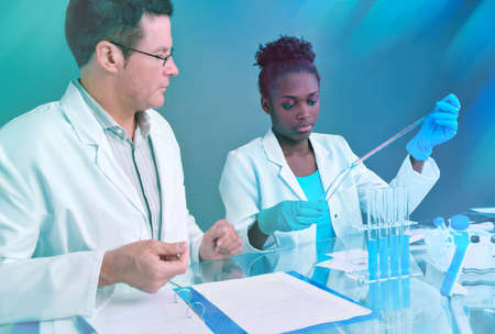 Scientists, senior Caucasian male and young African female, work together on a joint project in histopathology research facility, neon toned image