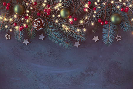 Christmas background with fir twigs, red berries, cones and Xmas lights on dark abstract background with copy-space Stock Photo