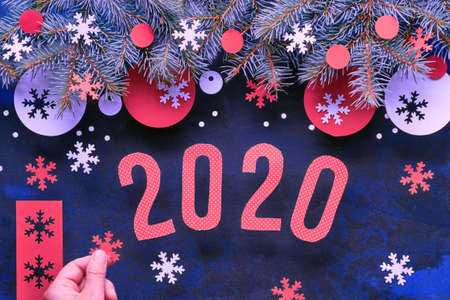 Hand holding paper snowflake. Christmas or New Year background with number 2020, fir twigs, red and white paper decorations. Flat lay, top view on dark abstract background. Foto de archivo