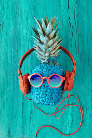 Funny pineapple painted blue in red in sunglasses and earphones. Flat lay on cracled wood painted turquoise.