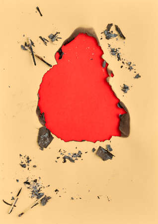 Burnt hole in yellow paper with burned edges, flat lay on red paper with copy-space