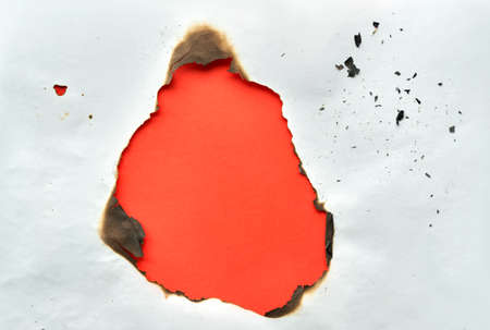 Burnt hole in crumpled white paper with burned edges, flat lay on vibrant orange paper with copy-space