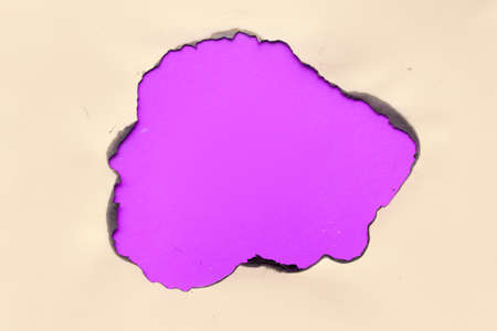 Burnt hole in beige paper with burned edges, flat lay on glowing purple paper
