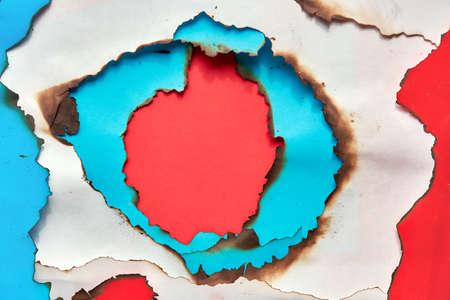 Hole burned though white, red and cyan or turquoise color paper. Abstract flat lay paper pattern with copy-space. 写真素材