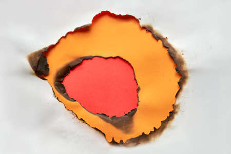 Burnt hole in white and orange paper with burned edges, flat lay on vibrant red paper background with copy-space