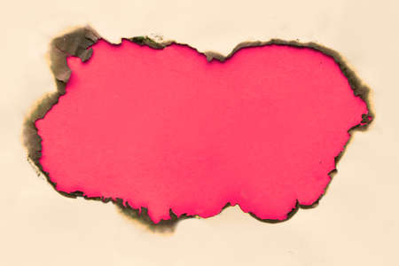Burnt hole in yellow paper with burned edges, flat lay on crimson red paper with copy-space 写真素材