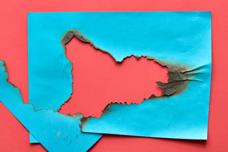 Burnt hole in turquoise and red paper with burned edges, flat lay with copy-space