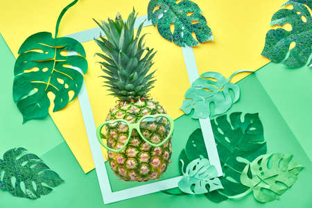 Funny pineapple in sunglasses, frame and paper exotic leaves in neo mint, green and yellow colors. Text space in paper frame Banque d'images
