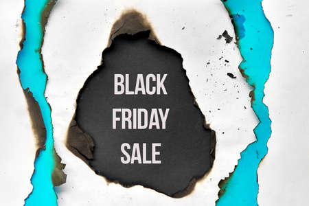 Text Black Friday Sale in burnt hole in white and turquoise paper with burned edges, flat lay on black paper