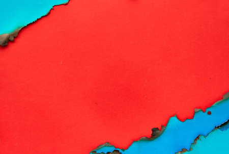 Mint color paper frame with burned edges, flat lay on vibrant red paper with copy-space 写真素材