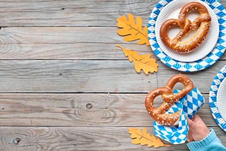 Oktoberfest, female hand in blue sweater holding pretzel. Flat lay on rustic wooden table with blue and white checkered disposable paper plates and orange Autumn leaves and copy-space. Stock Photo