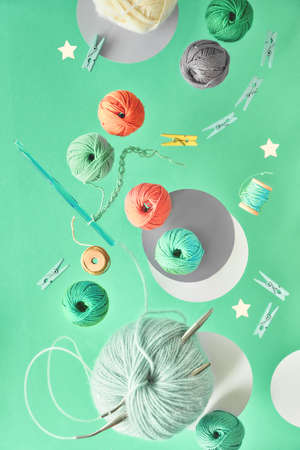 Various wool yarn and knitting needles, creative knitting hobby background in pastel colors on paper with copy-space Banco de Imagens