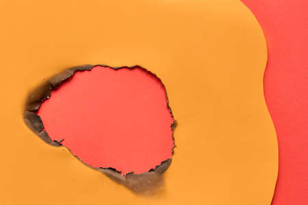 Burnt hole in orange paper with burned edges, flat lay on vibrant red paper background with copy-space