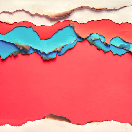 Layered turquoise, beige and crimson red paper with burned edges, flat lay, square composition with copy-space on red background