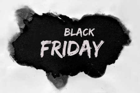 Text Black Friday Sale in burnt hole in white paper with burned edges, flat lay on black paper