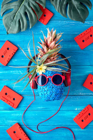 Hipster pineapple character in red sunglasses and earphones listens to the music. Rustic textured wooden blue background with red audio cassettes and exotic monstera leaves, flat lay, top view. Retro disco music concept.