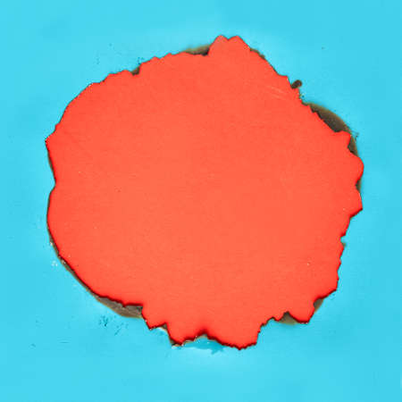 Burnt hole in turquoise paper with burned edges, flat lay on vibrant orange paper with copy-space Banco de Imagens