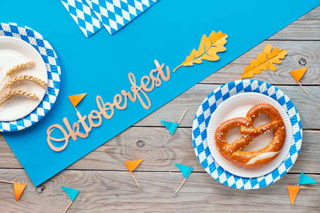 Oktoberfest, flat lay on rustic wooden table with blue paper spread, pretzels on disposable plates with blue white Bavarian pattern, decorative flags, wheat ears and Autumn leaves