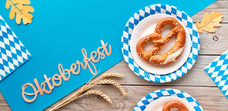 Oktoberfest, flat lay on rustic wooden table with blue paper spread, pretzels on disposable plates, wheat ears, decorative flags and Autumn leaves. Top view, panoramic banner composition.