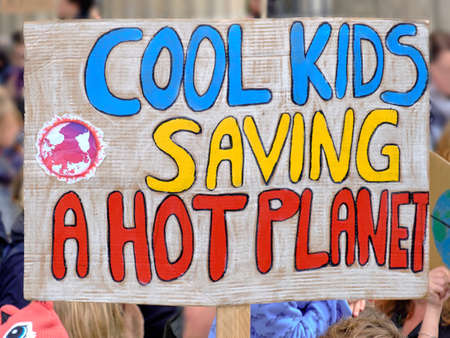 "Placard ""Cool kids saving a hot planet"" on global climate strike in Berlin, Germany"