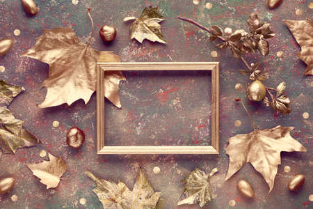 Autumn flat lay baackground with sycamore leaves, acorns and chestnuts painted gold. Copy-space in golden frame on dark textured canvas. Top view with text space. Stok Fotoğraf