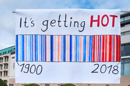 "Global climate strike in Berlin, Germany. Placard ""It's getting hot"" with temperature chart on a rally by Brandenburg Gate."
